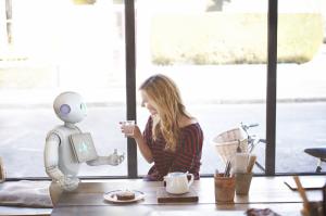 Le robot Pepper en pleine conversation avec une jeune femme au petit déjeuner